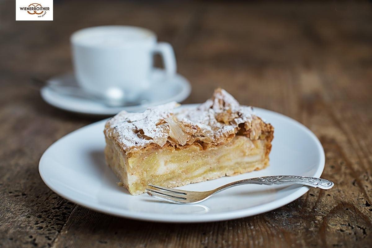 ein hausgemachter Apfelstrudel von der Bäckerei Wienerroither, serviert auf einem weißen Teller mit einer silbernen Kuchengabel. im Hintergrund eine Kaffeetasse