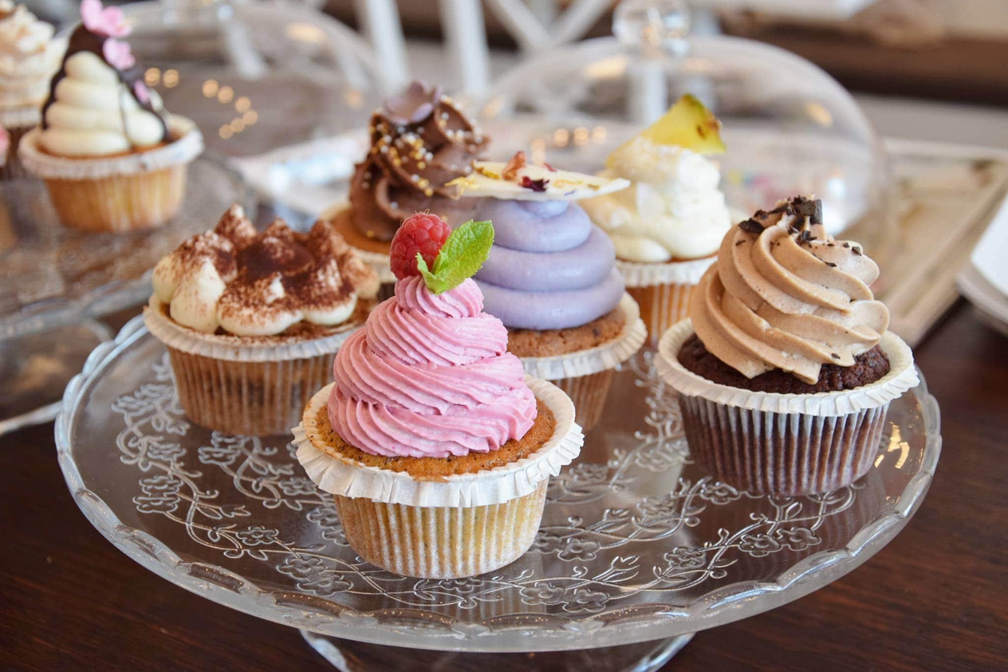 ein Glasteller mit verschiedenen Cupcakes von Rose Cupcake Shop & Cafe in Klagenfurt. Sie haben unterschiedlichen Kuchenteig und verschiedenfarbige Toppings verziert mit Beeren, Schokolade, Streusel und Kakao