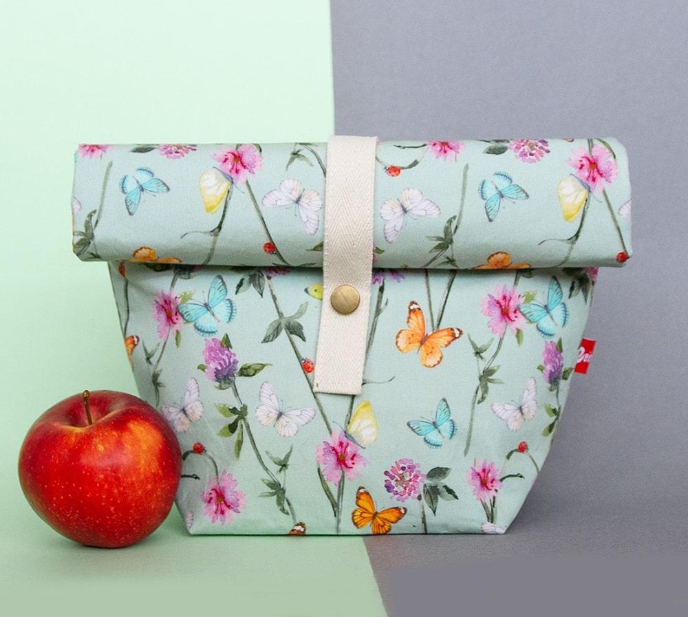ein mintfarbener Lunchbag mit Blumen und Schmetterlingsaufdruck und einem Verschlusss mit Druckknopf, Design aus Klagenfurt von Veinzelstück, daneben ein Apfel