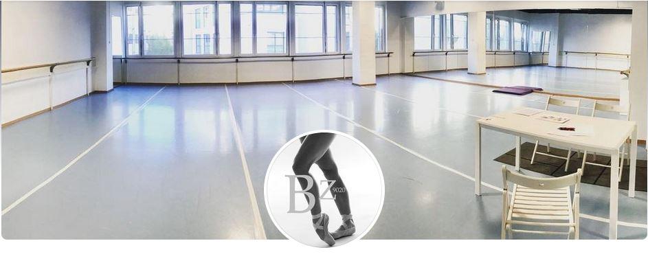 ein Blick in den Ballettssal des Ballettzentrum Klagenfurt, entlang der großen Fensterfront ist ene Ballettstange befestigt, an einer Wand ist eine große Spiegelfront, vorne rechts steht ein weißer Schreibtisch mit einem Sessel