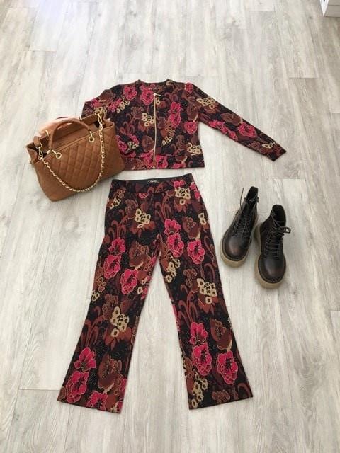 Herbstmode von BonBon Klagenfurt, ein Hosenanzug mit Hose und Blazer in erdfarben mit dunkelroten Blumen, dazu eine braue Tasche und dunkelbraune Boots