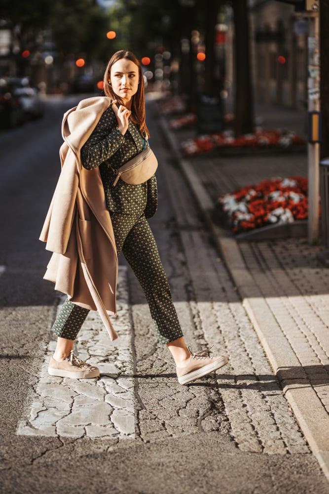 Herbstmode von Bon Bon in Klagenfurt. Das Model überquert einen Zebrastreifen in der Bahnhofstraße und trägt dabei einen Hosenanzug in dunkelgrün mit gelben, kleinen Blumen. Lässig über die Schulter gelegt hält sie einen carmelfarbenen Mantel