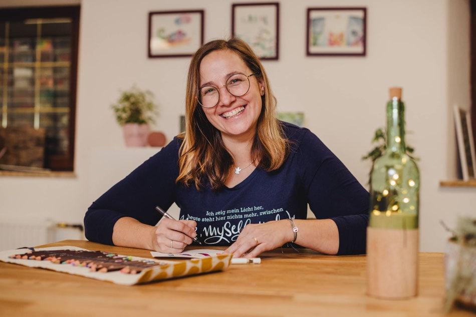 die Glückskleckserin Melanie Riemer sitzt an ihrem Tisch mit einem Stifteset und schreibt, dabei lächelt sie in die Kamera